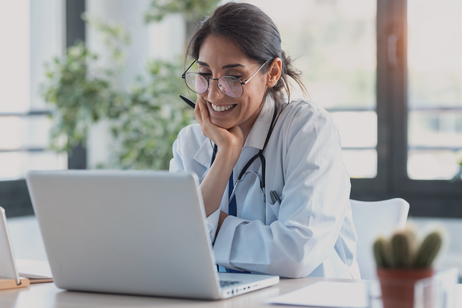 Doctor Smiling Looking at Laptop Screen in Office