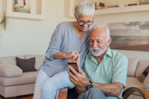 Two Seniors Smiling Sitting on Chair Looking at Phone