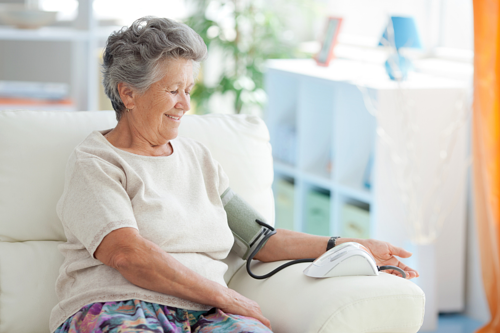 Woman Sitting on Couch Taking Blood Pressure Reading